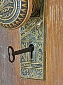 12012824-this-is-a-retro-metal-intricate-design-doorknob-with-the-metal-key-in-the-keyhole-to-unlock-the-wood