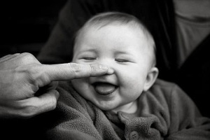 finger touching nose of baby